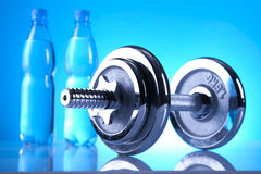 Fitness equipment. Iron dumbell and bottles of mineral water Royalty Free Stock Images