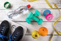 Fitness equipment and accessories on white wood background royalty free stock images