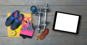 Fitness equipment and blank digital tablet on gym floor Stock Photography