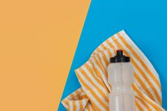 Fitness equipment bottles and towels on yellow background stock images