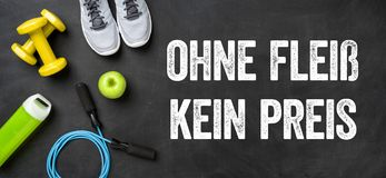 Fitness equipment on a dark background - No pain no gain - Ohne Fleiss kein Preis German royalty free stock image