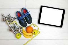 Fitness equipment and fruits on white wooden plank floor Royalty Free Stock Photography