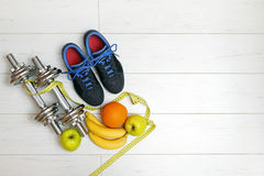 Fitness equipment and fruits on white wooden plank floor Royalty Free Stock Images