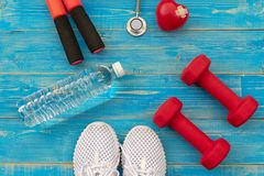 Fitness equipment gym workout and fresh water with heart and medical stethoscope on the blue background, top view and copy space royalty free stock images