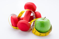Fitness equipment. Healthy food. Apple, dumbbells and measuring tape on white background. View from above Stock Photography