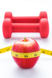 Fitness equipment. Healthy food. Apple, dumbbells and measuring tape on white background. View from above Stock Photo