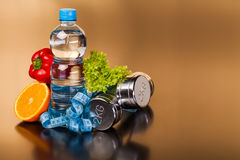 Fitness equipment and healthy food. On black surface Stock Photos