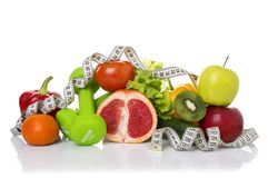 Fitness equipment and healthy food. Isolated on white. green apple, pepper, kiwi, dumbbells and measuring tape Stock Image