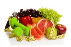 Fitness equipment and healthy food. Isolated on white. green and red apples, pepper, grapes, grapefruit, parsley, nectarines, dumbbells and measuring tape Royalty Free Stock Photography