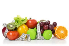 Fitness equipment and healthy food. Isolated on white. apple, pepper, grapes, kiwi, orange, dumbbells and measuring tape Stock Photo