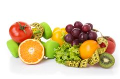 Fitness equipment and healthy food. Isolated on white. green apple, pepper, grapes, nectarines, kiwi, orange, dumbbells and measuring tape Stock Image