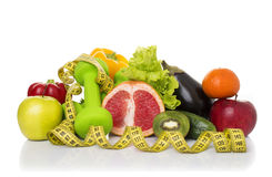 Fitness equipment and healthy food. Isolated on white. green apple, pepper, kiwi, dumbbells and measuring tape Stock Photo