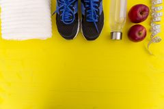 Fitness equipment. Healthy food. Sneakers, water,apple, measurin. G tape on yellow wooden background Stock Photo
