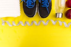 Fitness equipment. Healthy food. Sneakers, water,apple, measurin. G tape on yellow wooden background Royalty Free Stock Photography