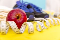 Fitness equipment. Healthy food. Sneakers, water,apple, measurin. G tape on yellow wooden background Royalty Free Stock Photo