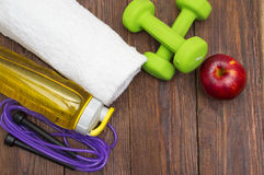 Fitness equipment. Healthy food. Sneakers, water, skipping rope and apple. On wooden background. Fitness concept Stock Images