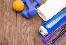 Fitness equipment. Healthy food. Sneakers, water, skipping rope and orange. On wooden background. Fitness concept Royalty Free Stock Images