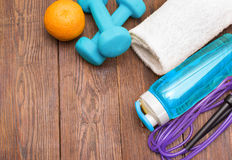 Fitness equipment. Healthy food. Sneakers, water, skipping rope and orange. On wooden background. Fitness concept Stock Photography