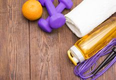 Fitness equipment. Healthy food. Sneakers, water, skipping rope and orange. On wooden background. Fitness concept Royalty Free Stock Photo