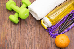 Fitness equipment. Healthy food. Sneakers, water, skipping rope and orange. On wooden background. Fitness concept Stock Images