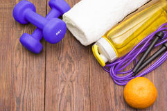 Fitness equipment. Healthy food. Sneakers, water, skipping rope and orange. On wooden background. Fitness concept Royalty Free Stock Photography