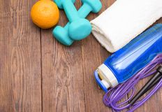 Fitness equipment. Healthy food. Sneakers, water, skipping rope and orange. On wooden background. Fitness concept Stock Image