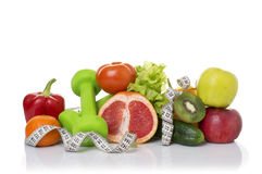 Fitness equipment and healthy food. On white. green apple, pepper, grapes, nectarines, kiwi, orange, dumbbells and measuring tape Stock Photo