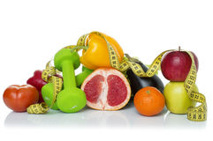 Fitness equipment and healthy food. On white. green apple, pepper, kiwi, dumbbells and measuring tape Stock Image