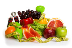 Fitness equipment and healthy food. On white. green and red apples, pepper, grapes, grapefruit, parsley, nectarines, dumbbells and measuring tape Royalty Free Stock Photos