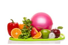 Fitness equipment and healthy food  on white. Green and red apples, pepper, grapes, grapefruit, parsley, nectarines, dumbbells and measuring tape Stock Image