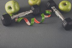 Fitness equipment and healthy lifestyle concept. Fitness equipment. Healthy lifestyle. Dumbbells, apple and measuring tape on gray background Stock Image
