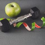 Fitness equipment and healthy lifestyle concept. Fitness equipment. Healthy lifestyle. Dumbbells, apple and measuring tape on gray background Stock Photography