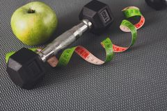 Fitness equipment and healthy lifestyle concept. Fitness equipment. Healthy lifestyle. Dumbbells, apple and measuring tape on gray background Royalty Free Stock Image