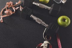 Fitness equipment and healthy lifestyle concept. Fitness equipment. Healthy lifestyle. Dumbbells, water, apple and measuring tape on black background, copy space Royalty Free Stock Photos