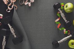 Fitness equipment and healthy lifestyle concept. Fitness equipment. Healthy lifestyle. Dumbbells, water, apple and measuring tape on black background Stock Images