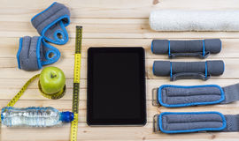 Fitness Equipment And Healthy Nutrition. Sport Equipment. Dumbbells,  Ankle Weights, Wrist Weights, Towel, Tape Measure, Apple, Bottle Of Water And Tablet To Royalty Free Stock Photo