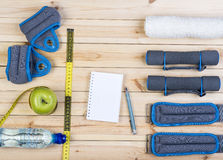 Fitness Equipment And Healthy Nutrition. Sport Equipment. Dumbbells,  Ankle Weights, Wrist Weights, Towel, Tape Measure, Apple, Bottle Of Water And Notebook To Royalty Free Stock Images
