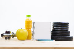 Fitness Equipment And Healthy Nutrition. Sport Equipment. Free Weights, Barbell, Apple, Orange Juice  And Notepad To Workout Plan On Wooden Table. Sport Fitness Stock Photos
