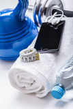 Fitness Equipment. Kettlebell towel dumbbells water smart phone with headphones and measuring tape Royalty Free Stock Images