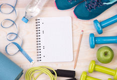 Fitness equipment and notebook on wooden background Stock Image
