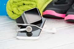 Fitness equipment, smart watch and phone. Royalty Free Stock Image