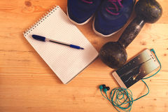 Fitness equipment and training plan on table Royalty Free Stock Photo
