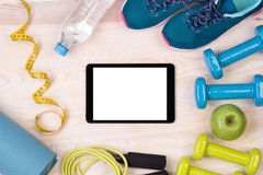 Fitness equipment on wooden background with a tablet royalty free stock photo