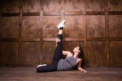 Fitness and exercice concept. Beautiful brunette lying on floor and doing exercises. Sport concept Royalty Free Stock Photography