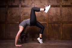 Fitness and exercice concept. Girl isolated on wooden background. Doing bridges exercises Stock Photography