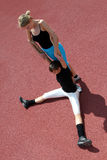 Fitness exercises. Two young athletes stretching each other Royalty Free Stock Photography