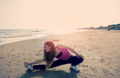Fitness exercises on the beach at sunset warm filter applied Royalty Free Stock Photos