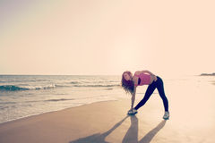 Fitness exercises on the beach warm filter applied Royalty Free Stock Photos