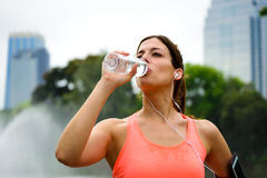 Fitness female athlete driking water on workout rest Stock Images