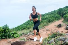 Fitness female athlete running on forest path in mountainous area in summer. Sporty woman working out going uphill. Fitness female athlete running on forest Stock Images